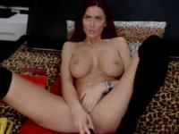 A big breasted brunette is getting naked while teasing