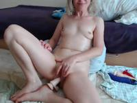 Fake blonde with a shaved cunt toys with herself