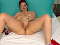 A fat chick is on the bed