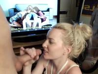 Blonde does a blowjob while porn is on TV