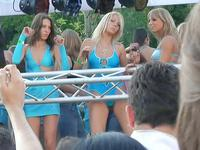 Beautiful girls in hot sexy swimsuits are erotically moving their bodies at the parade