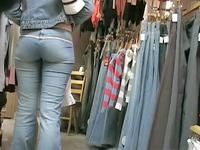 The delicious girl in tight jeans is in the store choosing a new pair of the hot pants